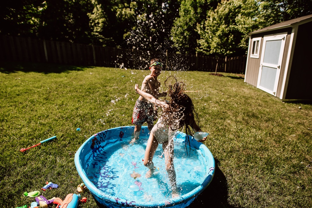 Kid pool water balloon splash backyard summertime documentary photography