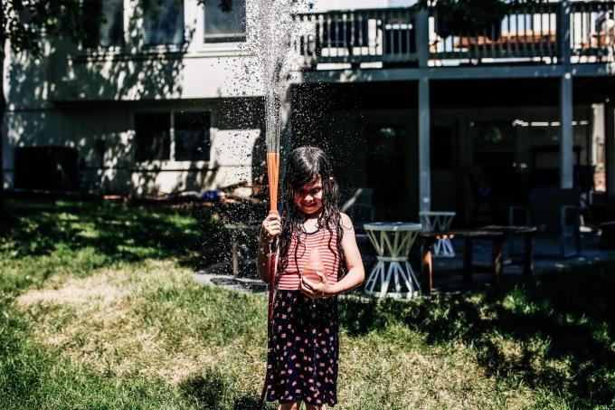 girl hose splash backyard documentary photography summertime