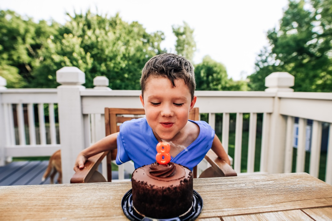 birthday boy blowing out candles on cake